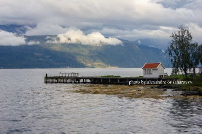 A small wooden red-white house on the shore of the fjord. Balestrand. Norway