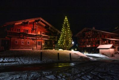 My trip to Austria. Kaprun Village. Christmas tree near wooden houses